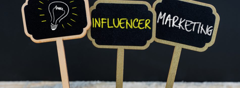 Concept message INFLUENCER MARKETING and light bulb as symbol for idea written with chalk on wooden mini blackboard labels defocused chalkboard and wood table in background